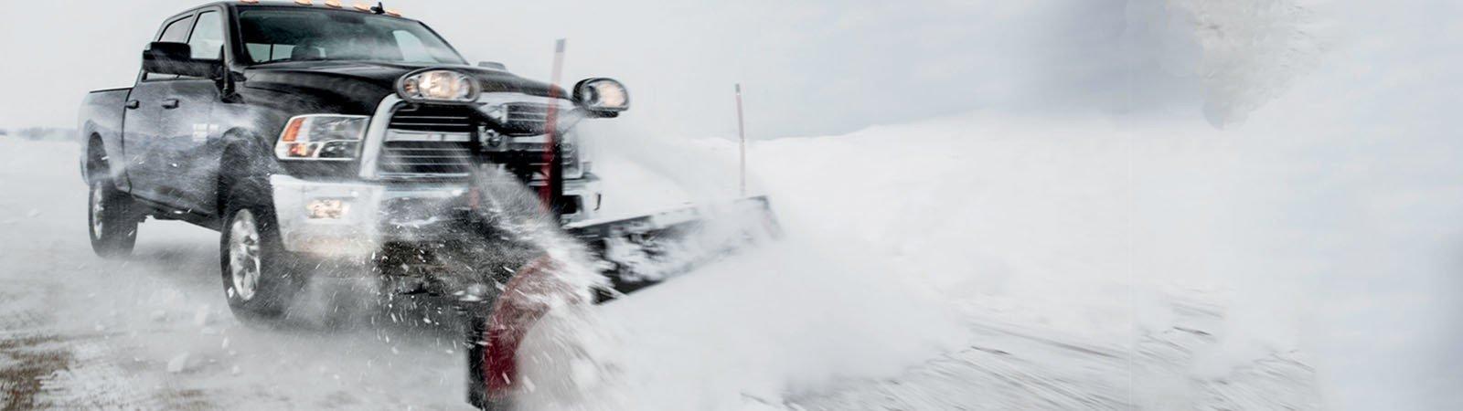 RAM truck plowing snow on a snowy road